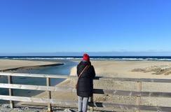 Strand met vrouw die op een houten leuning rusten en de mening bekijken De winterkleren en rode hoed Zonnige dag, blauwe overzees royalty-vrije stock afbeeldingen