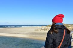 Strand met vrouw die op een houten leuning rusten en de mening bekijken De winterkleren en rode hoed Zonnige dag, blauwe overzees stock foto's
