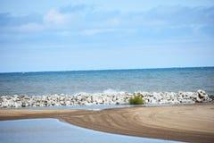 Strand met zand againt Overzees Stock Foto