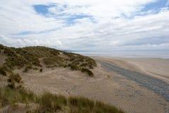 Strand met zand, kiezelstenen en duinen Stock Foto's