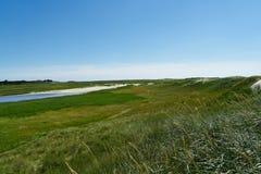 Strand met zandduinen en een weg aan het overzees Stock Foto's