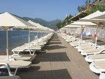 Strand met zon-tenten en zon-bedden Stock Foto
