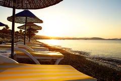 Strand met zonsondergang en zonbedden Stock Afbeeldingen