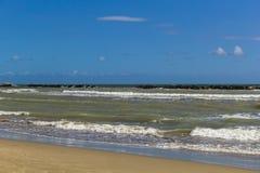 Strand mit dem Meer gerüttelt Stockfoto