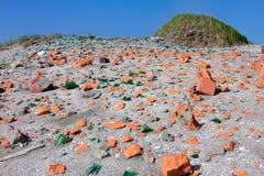 Strand mit Glasscherben und Ziegelstein Stockbild