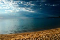 Strand mit Meer mit Regenwolken Lizenzfreies Stockfoto