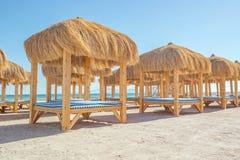 Strand mit mit Stroh gedeckten Gazebo- und Sonnenruhesesseln Stockfoto