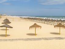 Strand mit rusitc Strohsonnenschutz Lizenzfreie Stockfotos