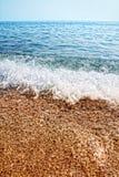 Strand mit sauberen Kieseln und Wellen Stockfotos