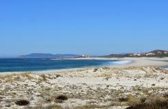 Strand mit See, Vegetation in den Sanddünen und Leuchtturm Klares Wasser mit Wellen und Schaum Grüne, Blau- und Türkisfarben blau lizenzfreie stockfotografie