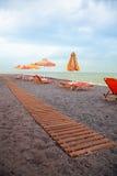 Strand mit Sonnestühlen und -gehweg Stockfotos