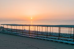 Strand am Morgen mit Sonnenruhesesseln Stockbilder