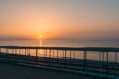 Strand am Morgen mit Sonnenruhesesseln Lizenzfreie Stockfotos