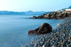 Strand mot blått vatten Arkivfoton