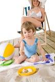 Strand - Mutter mit Kinderspiel mit Spielwaren im Sand Lizenzfreie Stockbilder