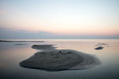 Strand na de zonsondergang met zand en wolken Stock Foto
