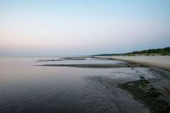 Strand na de zonsondergang met zand en wolken Royalty-vrije Stock Fotografie