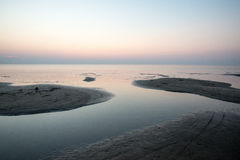 Strand na de zonsondergang met zand en wolken stock fotografie