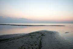 Strand na de zonsondergang met zand en wolken Royalty-vrije Stock Foto
