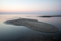 Strand na de zonsondergang met zand en wolken stock afbeelding