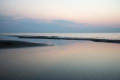 Strand na de zonsondergang met zand en wolken Royalty-vrije Stock Afbeelding