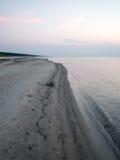 Strand na de zonsondergang met zand en wolken stock afbeeldingen