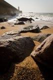 Strand nahe Leuchtturm Stockfoto