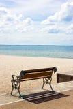Strand och bänk i solig dag Arkivfoton
