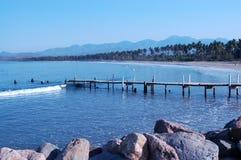 Strand och gammal fiskepir längs kustlinjen Arkivfoton