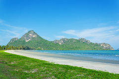Strand och hav med bergbakgrund Arkivfoto