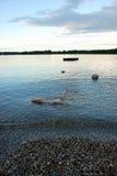 Strand op meer na zonsondergang Stock Foto's