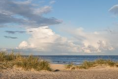 Strand, Ozean und blauer Himmel mit Wolken bei Grenen Skagen in Dänemark lizenzfreie stockfotografie