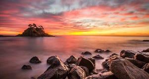 Strand på den härliga solnedgången Arkivfoto