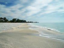 Strand på en solig dag med blått vatten royaltyfri bild