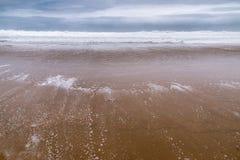 Strand på lågvatten under en stormig himmel Arkivfoto