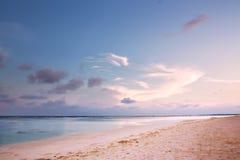 Strand på skymning med rosa färgsand Arkivbilder
