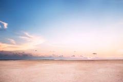 Strand på skymning med rosa färgsand under blå himmel Arkivbild