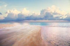 Strand på skymning med vatten för rosa färgsand- och rosa färgperple Arkivbilder