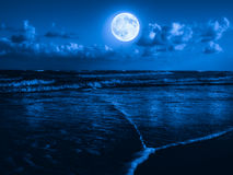 Strand på midnatt med en fullmåne Fotografering för Bildbyråer