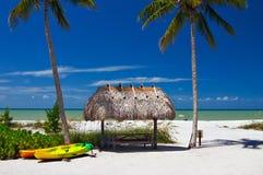 Strand-Paradies mit Regenschirm Stockbild