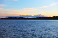 Pink Cumulous Clouds over Blue Water at Sunset. Strand of puffy cumulus clouds glow agains pink sky as sun sets in Puget Sound Royalty Free Stock Image