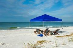 Strand-Schutz und Stühle Stockfotos