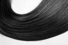 A strand of shiny healthy black hair stock photography