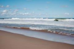 strand som bryter sandiga waves Royaltyfri Bild