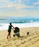 Strand som går med barnvagn Arkivfoto
