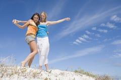 strand som kopplar av två unga kvinnor Royaltyfri Bild