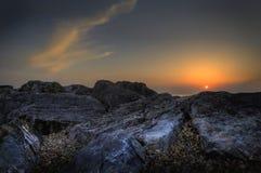 strand som är härlig över den vibrerande rockssolnedgången Royaltyfri Bild