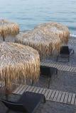 Strand-Stühle auf Kiesel-Sand-Strand bei Sonnenuntergang Stockfotografie