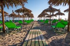 Strand-Stühle mit Regenschirmen Stockfotos