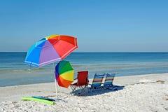 Strand-Stühle mit Regenschirmen Lizenzfreies Stockbild